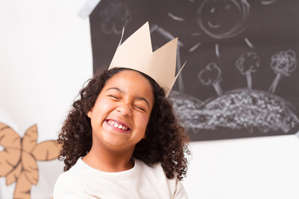 Child girl with paper crown making gesture face
