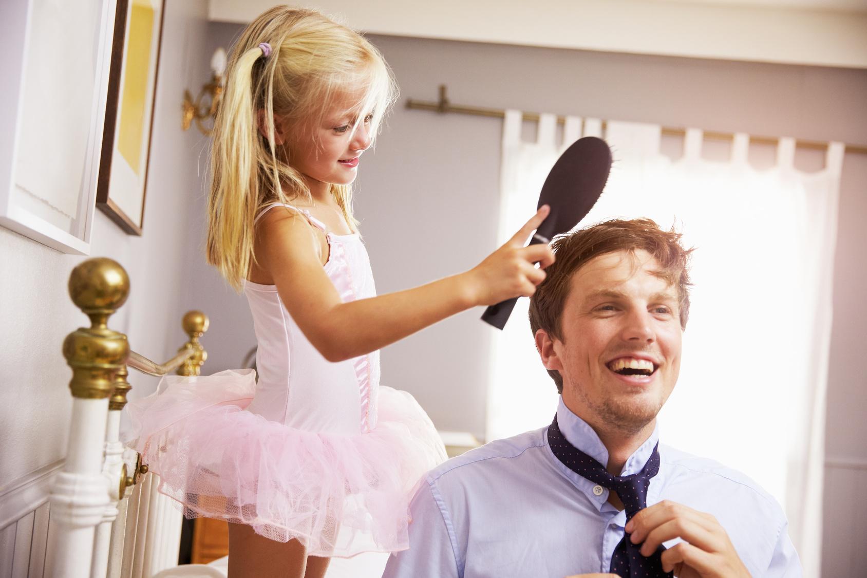 Fillette en robe de princesse qui peigne papa