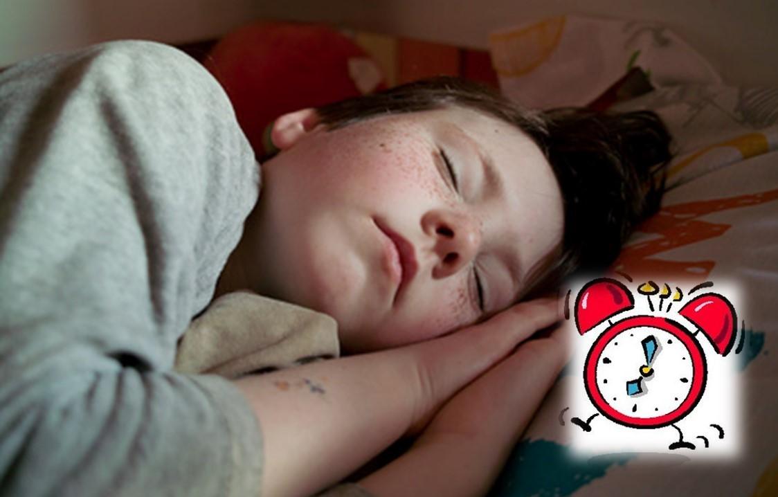 Garçon qui dort profondément avec réveil-matin